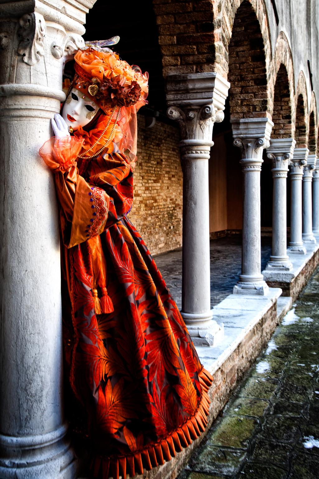 Carnival model in an orange costume by pillars