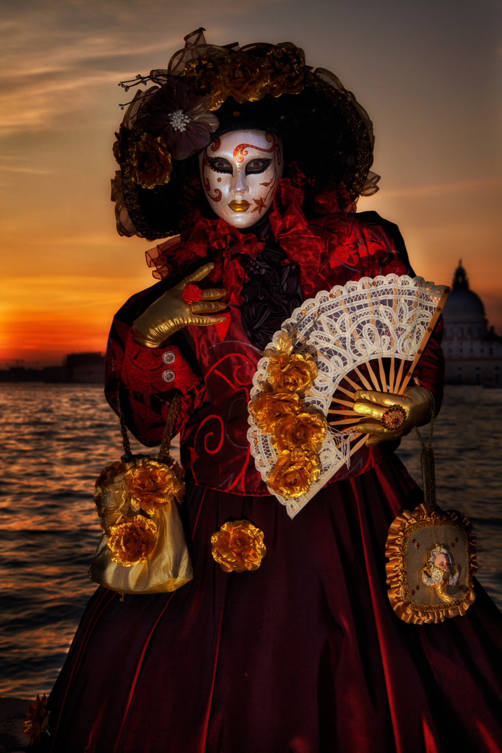 Mysterious looking Carnival model in front of a bright orange sunset
